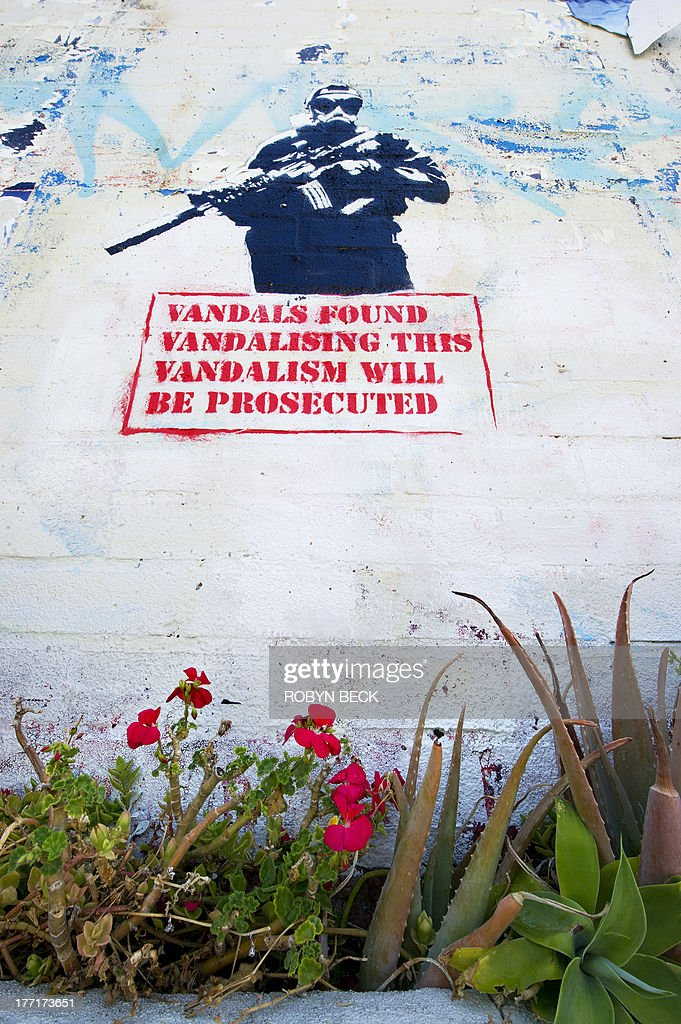 A street art stencil showing a soldier brandishing a machine gun above the slogan Vandals found vandalising this vandalism will be prosecuted' is seen on a wall in Los Angeles, California on August 21, 2013. The piece is by the artist Strömberg, although it has been mistaken in online forums to be by Banksy. Owners of the property have indicated they plan to remove the illegal artwork. AFP PHOTO / Robyn Beck