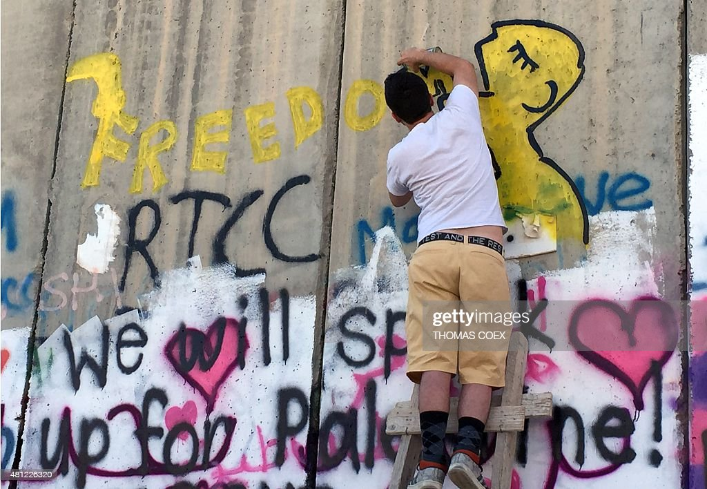 A US street artist coming from Iowa paints graffiti on the Israel's controversial separation barrier between the West Bank city of Bethlehem and...