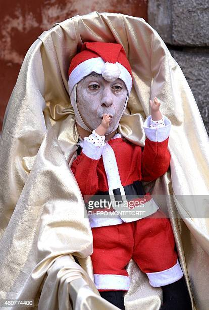 A street artist dressed as little Santa Klaus in a cradle stands in central Rome on December 22 2014 AFP PHOTO / FILIPPO MONTEFORTE