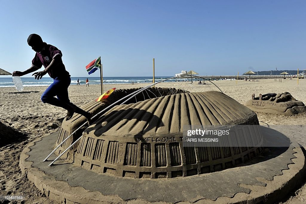 A street artist jumps out of a sand sculpture of Durban's soccer stadium for the South Africa 2010 World Cup at the beach of Durban, on June 5, 2010. AFP PHOTO / Aris Messinis