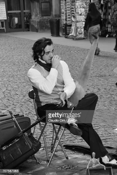 Street Artist Looking Away While Sitting On Chair