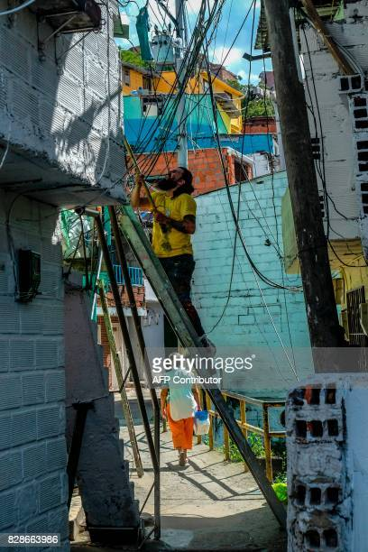 A street artist painst a wall at El Pesebre shantytown in the outskirts of Medellin Colombia on June 29 2017 French artist Tarik Bouanani turned 230...