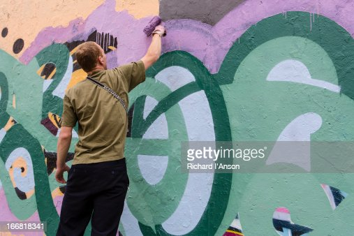Street artist painting on remnant of Berlin Wall