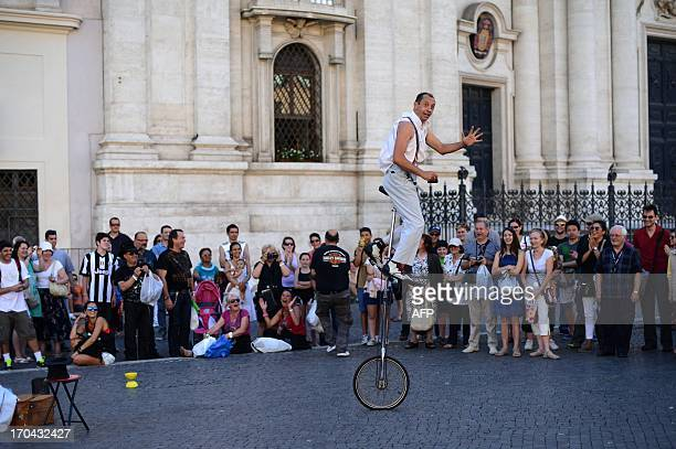 A street artist performs on a monowheel in front of tourists in Pazza Navona in Rome on June 12 2013 AFP PHOTO / BEATRICE DI CARO