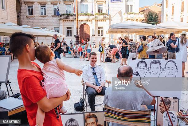 Street artist sketching portrait of tourists in Zadar, Croatia