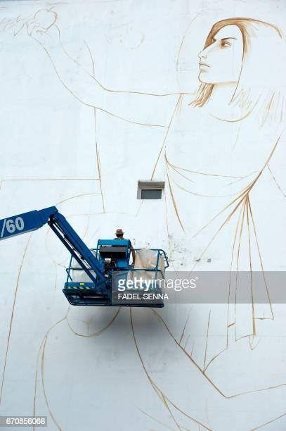 A street artist works on an mural during the 'Jidar' street art festival in the capital Rabat on April 20 2017 / AFP PHOTO / FADEL SENNA