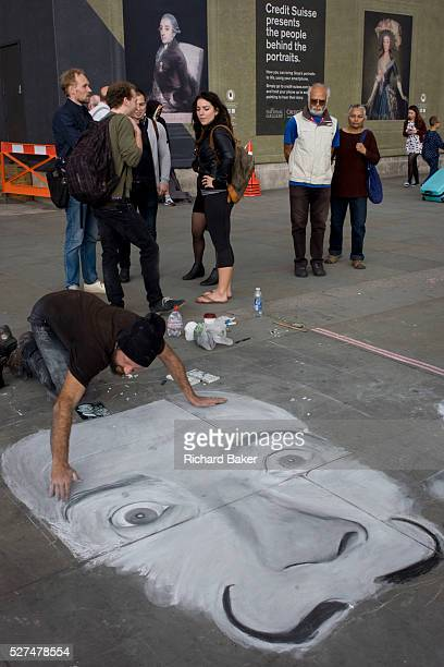A street artist works on his pavement piece in front of Goya portraits sponsored by Credit Suisse and advertised on a construction hoarding outside...