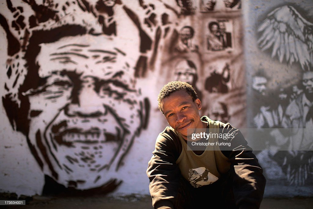 Street artist Xolani Mahlangu poses next to his stencil art of Nelson Mandela and other freedom icons in Soweto Township on July 16, 2013 in Soweto, Johannesburg, South Africa. Mahlangu is part of an artist collective called The Market Gallery who want to bring the history of anti-apartheid and the fight for freedom to the local youth of Soweto. Worldwide celebrations and charity events will mark Nelson Mandela's 95th birthday on July 18, as the anti-apartheid icon continues to be hospitalized at the Medi-Clinic Hospital in Pretoria suffering from a lung infection.