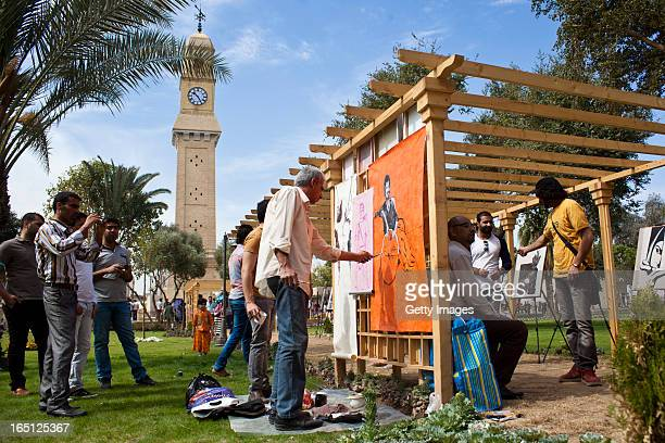 Street artists paint pictures in Qushla park outside the Baghdad Cultural Centre on March 29 2013 in Baghdad Iraq Ten years after the regime of...