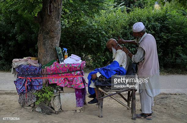 A street barber shaves his customers nape under a tree in Islamabad Pakistan on June 19 2015 Pakistanis prefer street barbers as they are cheaper...