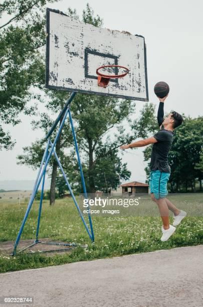 Street basketball player doing a slam dunk