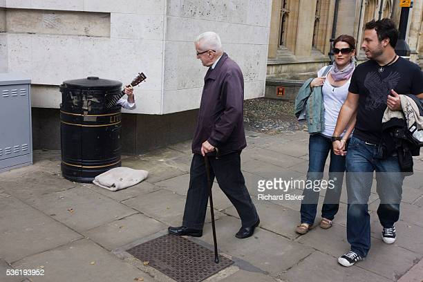 A street busker hides in a litter bin to earn extra cash as passersby hear his music on a Cambridge pavement As passersby walk past only the...