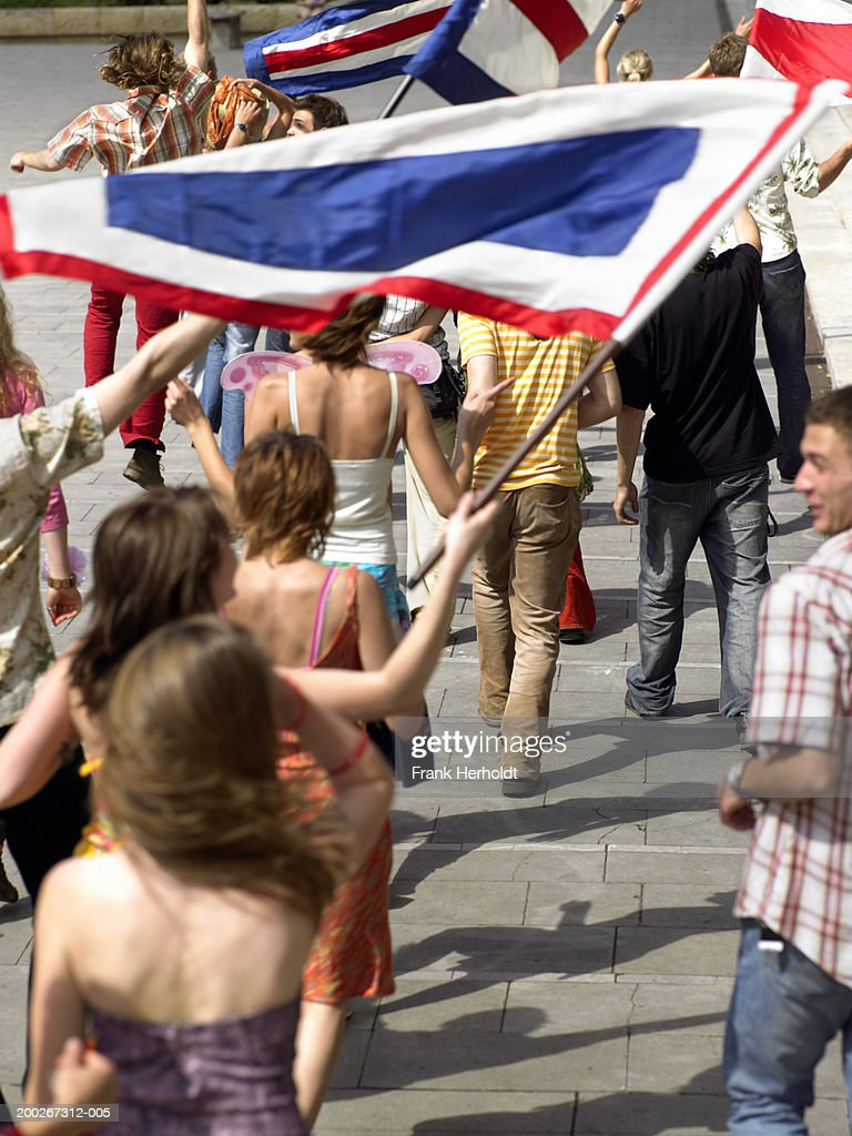 Street carnival procession waving flags, rear view (blurred motion) : Stock Photo