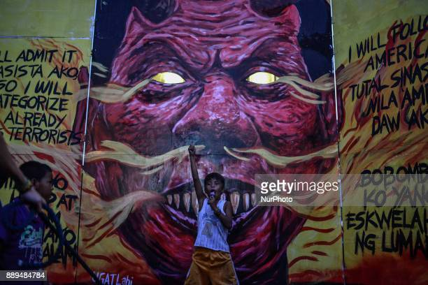 A street child plays in front of an effigy of Philippine President Rodrigo Duterte during Human Rights Day protests in Manila Philippines December 10...