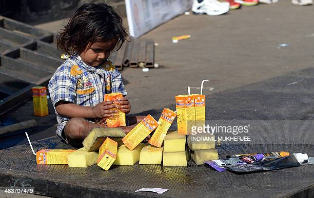 A street child plays with empty fruit drink packs thrown away by runners participating in the Mumbai Marathon on January 19 2014 Thousands of people...