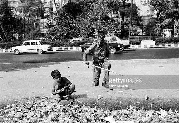 A street child who is searching for food at Chowpatti beach on Easter day is about to be beaten by a policeman