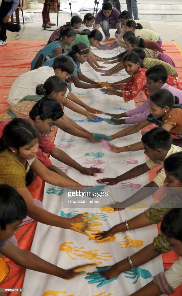 Street Children during their attempt of putting maximum handprints (9000 approx) on white cloth in minimum time of 15 minutes in the famed Limca Book of Records' at Bal Bhawan on April 12, 2013 in New Delhi, India. On International Day for Street Children, the hand print event was organised by NGO 'Chetana' at Bal Bhawan in central Delhi.