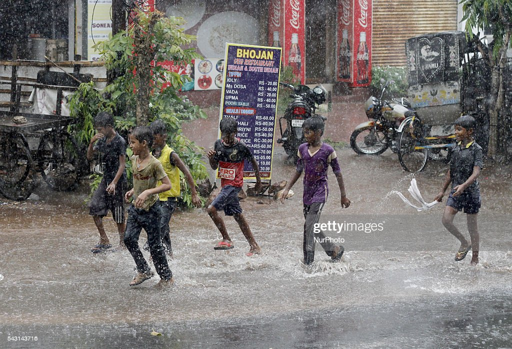 Street children look on road as they are enjoying rain as it rains in the eastern Indian city Bhubaneswar, India, Sunday, 26 June 2016.