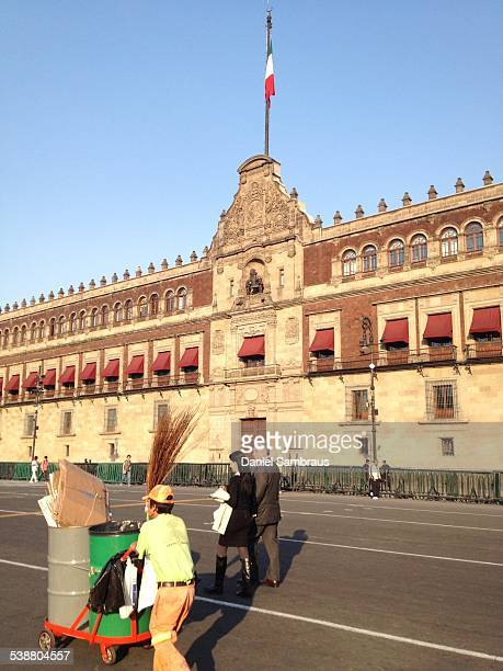 A street cleaner and pedestrians in front of the National Palace seat of the Mexican President and the federal executive in Mexico It is located on...