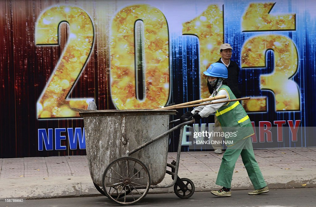 A street cleaner pushes a cart past a poster marking the 2013 new year in downtown Hanoi on December 28, 2012. Vietnam's economic growth slowed to the weakest pace in 13 years in 2012, according to published official statistics, piling more pressure on the country's rulers. Gross domestic product grew by 5.03 percent this year while inflation slowed to 6.8 percent in December year-on year from 7.08 percent in November. AFP PHOTO/HOANG DINH Nam