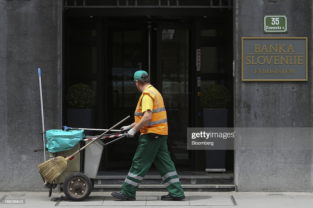 A street cleaner pushes his cart past the headquarters of the Slovenian central bank in Ljubljana, Slovenia, on Tuesday, May 7, 2013. Slovenia plans to increase taxes to make up for the swelling budget shortfall as the country works to recapitalize its banks. Photographer: Chris Ratcliffe/Bloomberg via Getty Images