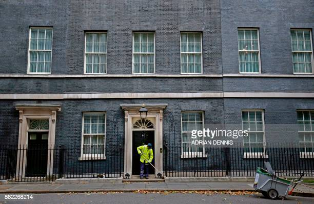 TOPSHOT A street cleaner sweeps the leaves from the doorstep of No 10 Downing Street in London on October 17 2017 / AFP PHOTO / ADRIAN DENNIS