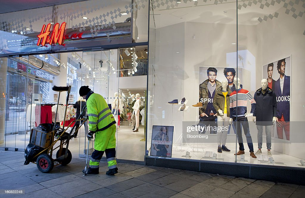 A street cleaner sweeps the sidewalk outside the entrance to a Hennes & Mauritz AB (H&M) store in Stockholm, Sweden, on Tuesday, Jan. 29, 2013. Hennes & Mauritz AB, Europe's second-largest clothing retailer, reported sales growth that beat analysts' estimates for a second consecutive month as the chain offered markdowns in advance of the Christmas holiday. Photographer: Casper Hedberg/Bloomberg via Getty Images