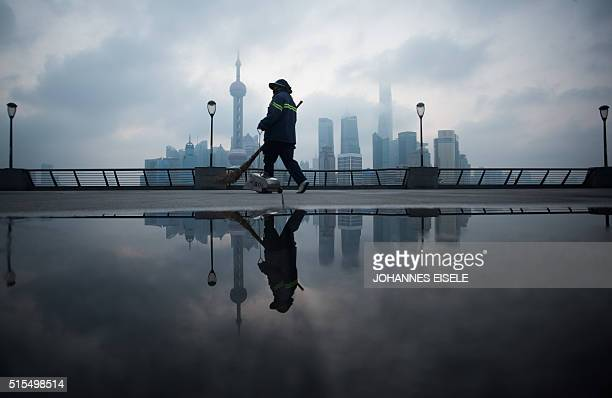 A street cleaner walks by the bund near the Huangpu river across the Pudong New Financial district in Shanghai on March 14 2016 China's leaders are...