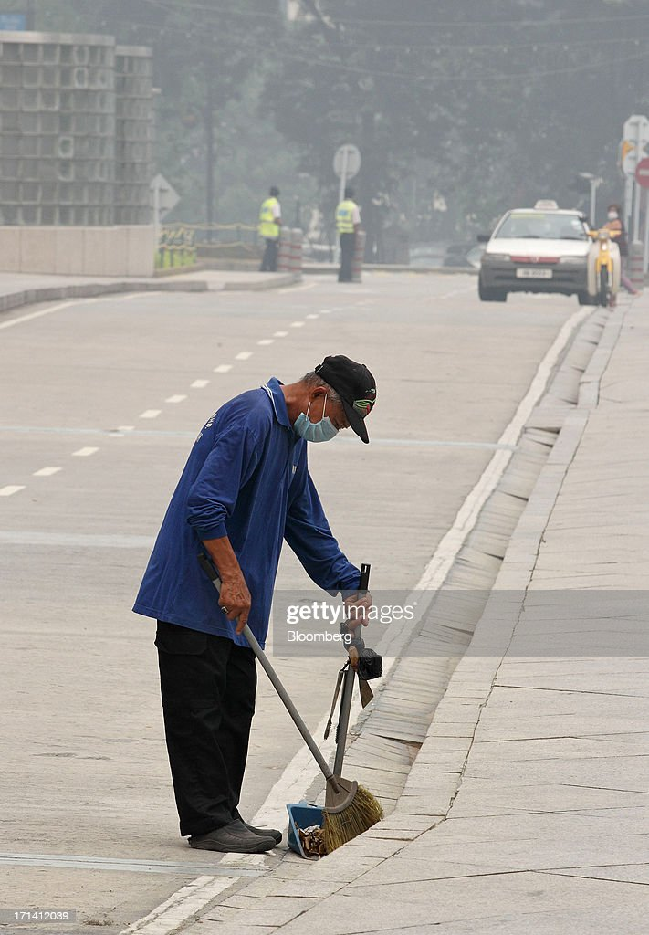 A street cleaner wears a face mask as he sweeps the side of a road in Kuala Lumpur, Malaysia, on Monday, June 24, 2013. Malaysia called for a meeting of Southeast Asian ministers as early as next week after haze from illegal Indonesian forest fires reached hazardous levels in parts of the region. Photographer: Goh Seng Chong/Bloomberg via Getty Images