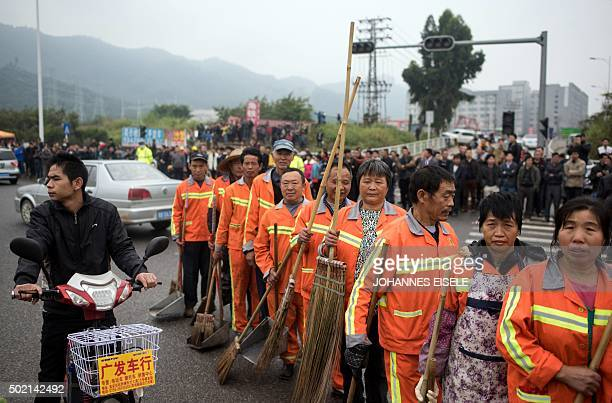 Street cleaners and onlookers stand on a street after a landslide hit an industrial park in Shenzhen south China's Guangdong province on December 21...