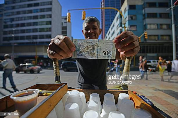 A street coffee vendor shows a new 500Bolivarnote in Caracas on January 16 2017 A new family of currency will progressively come into circulation in...