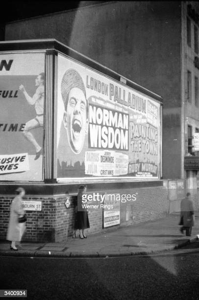 A street corner in Soho with a billboard poster advertising British comedian Norman Wisdom in 'Painting the Town' at the London Palladium