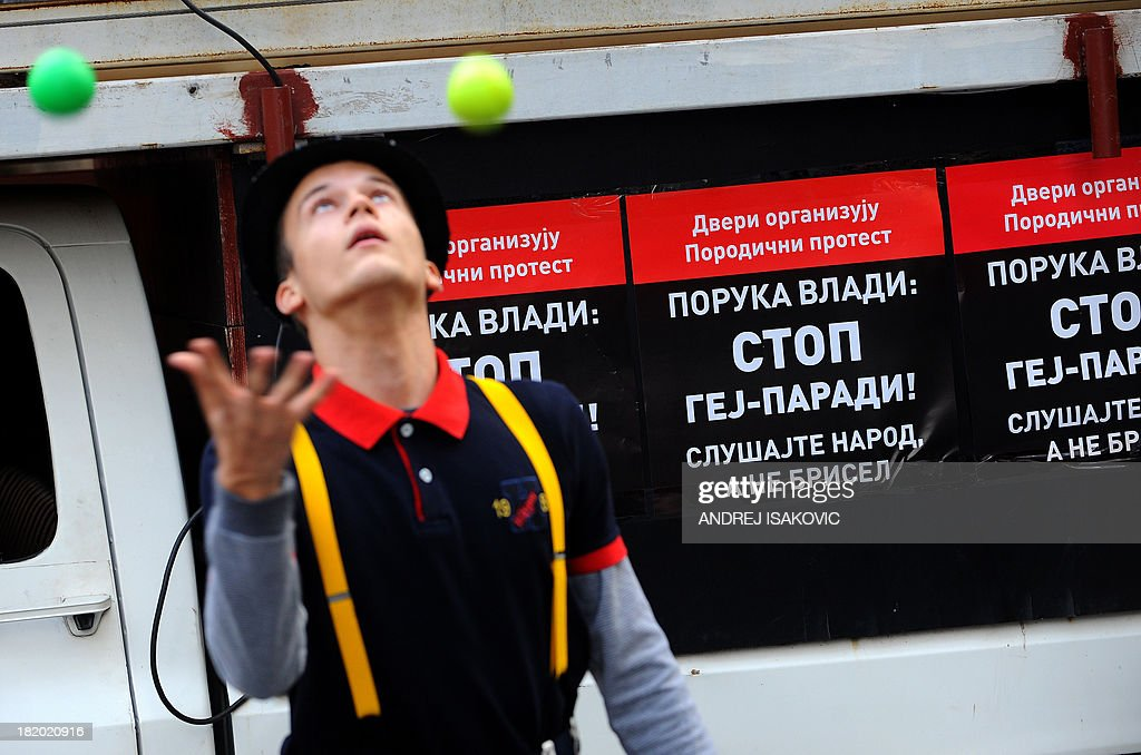 A street entertainer juggles during an anti-gay protest organised by Serbian ultra nationalists in Belgrade on September 27, 2013. Serbia's authorities on Friday banned for the third consecutive year Gay Pride, saying it was too high security risk to allow it. Several far-right organisations announced their intention to protest tomorrow at the time and the place where the parade is supposed to take place. Banner reads 'Stop gay pride parade'.