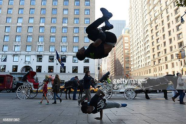 A street entertainers break dance on a footpath near Central Park in New York on November 4 2014 AFP PHOTO/Jewel Samad