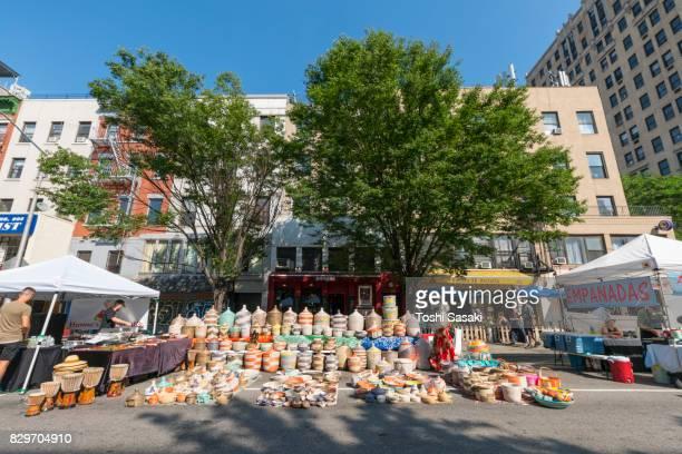 Street Fair was opened on the 2nd Avenue at East Village Manhattan New York on Jul. 16 2017. People walks down the 2nd Avenue among the many street shops along the street.