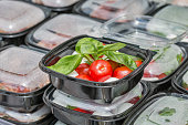 Street food box with mozzarella cheese, cherry tomatoes and basil closeup.