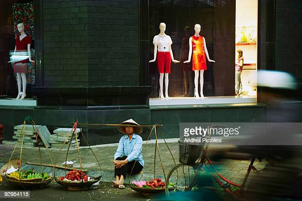 Street food vendor and modern clothes shop in Hanoi Old Town Vietnam