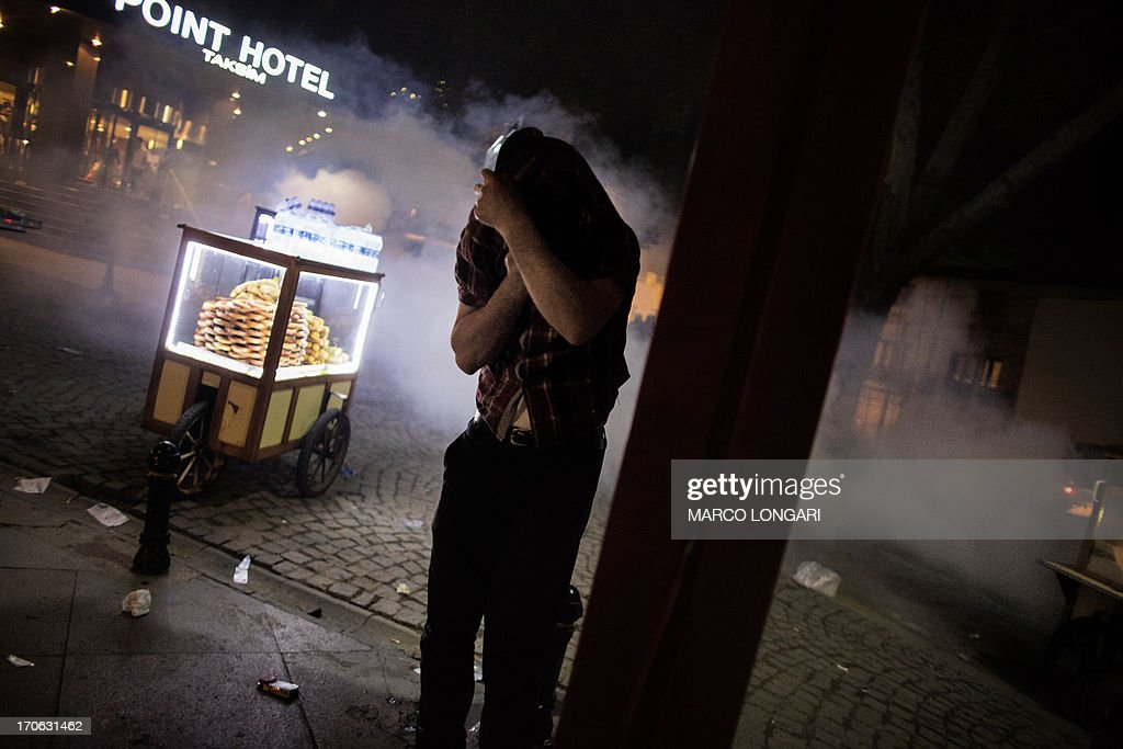 A street food vendor cover his face to protect himself from tear gas lobbed by Turkish riot police officers to disperse demonstrators in Gezi Park in Istanbul June 15, 2013.Turkish police stormed an Istanbul park on Saturday after protesters defied an ultimatum from Prime Minister Recep Tayyip Erdogan to end their occupation of the site, in a major escalation of more than two weeks of anti-government unrest.