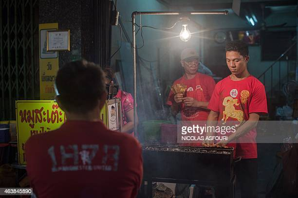 A street food vendor grillS chicken skewers for the Lunar New Year in the Chinatown area of Bangkok on February 19 2015 The Lunar New Year the most...