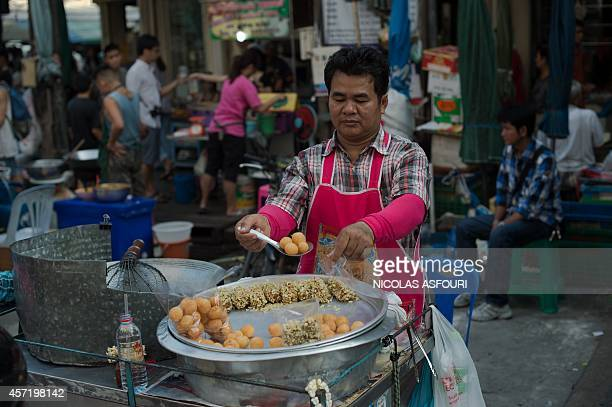 A street food vendor prepares takeaway bags of food in the Thai capital Bangkok on October 14 2014 Thailand's central bank held its key interest rate...