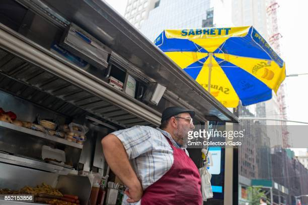 A street food vendor wearing an apron stands with his cart on 60th Street with hot dogs and other foods visible in the cart and a blue and yellow...