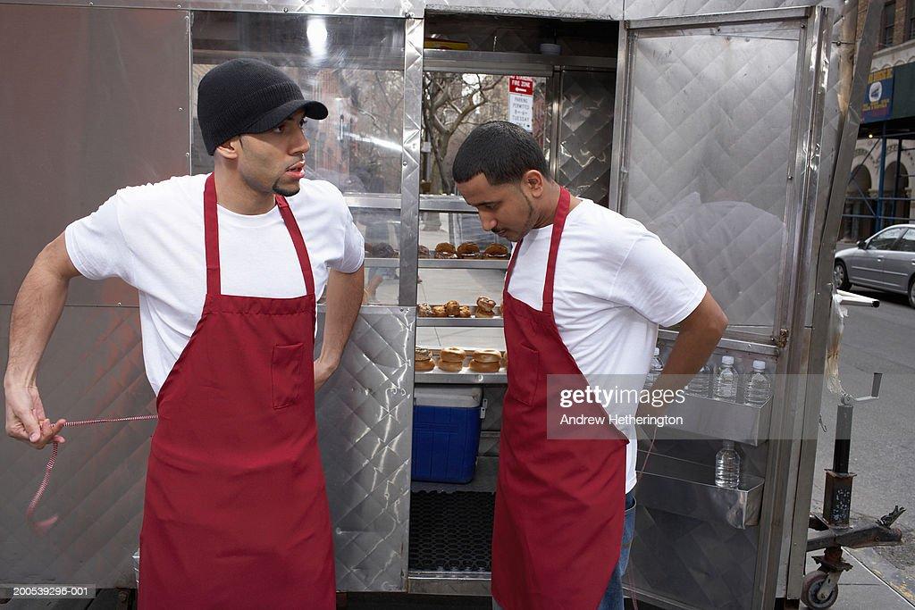 Street food vendors putting on aprons : Stock Photo
