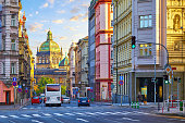 Street in Prague, Czech Republic. Cityscape with road and view at dome of national museum building. Transport and bus at crossroad. Dawn early morning in centre of city.