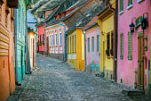 Rustic cobblestone street with colorful houses in old town Sighisoara.