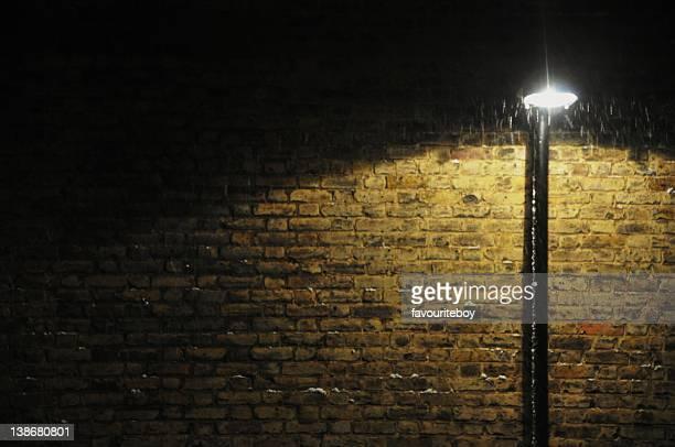 Street lamp by brick wall at night