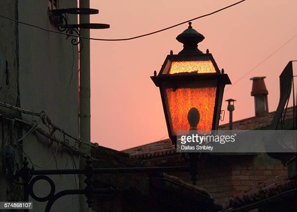 Street lantern glowing with the setting sun, Italy