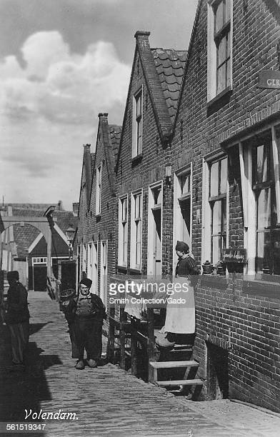 Street life a woman standing on her doorstep and a man walking along narrow cobbled street and a canal bridge in the distance Volendam Netherlands...