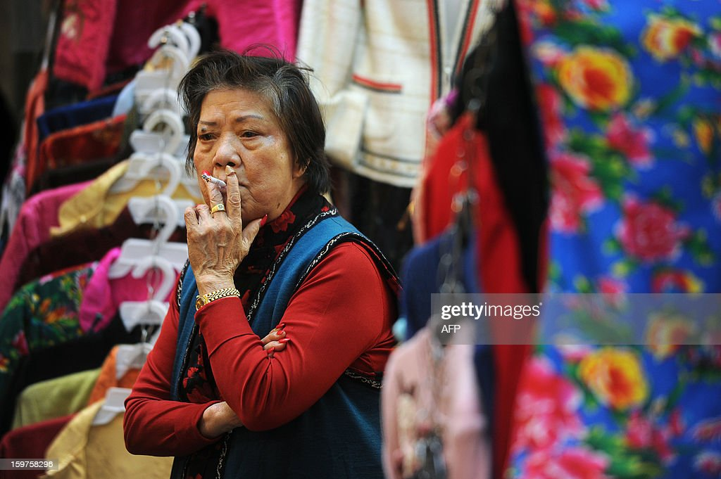 A street market vendor smokes a cigarette as she waits for customers at her clothes stall in Hong Kong on January 20, 2013. In a speech on January 16 widely seen as an attempt to address rising anti-Beijing sentiment and halt mass protests against his leadership, Chief Executive Leung Chun-ying pledged to increase housing supply, reduce choking pollution and tackle poverty.
