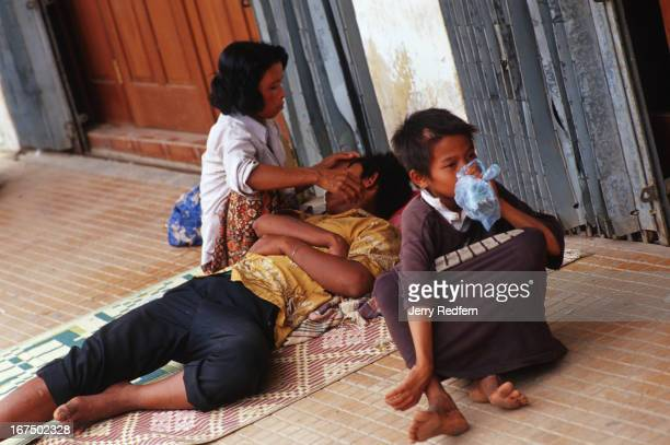 'Street Mom' Mao tends to her boyfriend Chhret who passed out after drinking rice wine Next to them Chhien huffs a bag of glue while hanging out with...