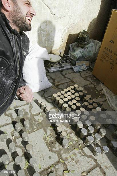 A street money exchange trader sits by coins brought to him to be exchanged for new Iraqi dinar notes without the face of ousted dictator Saddam...